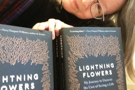 Naomi smiling with copies of the book Lightning Flowers by Katherine Standefer